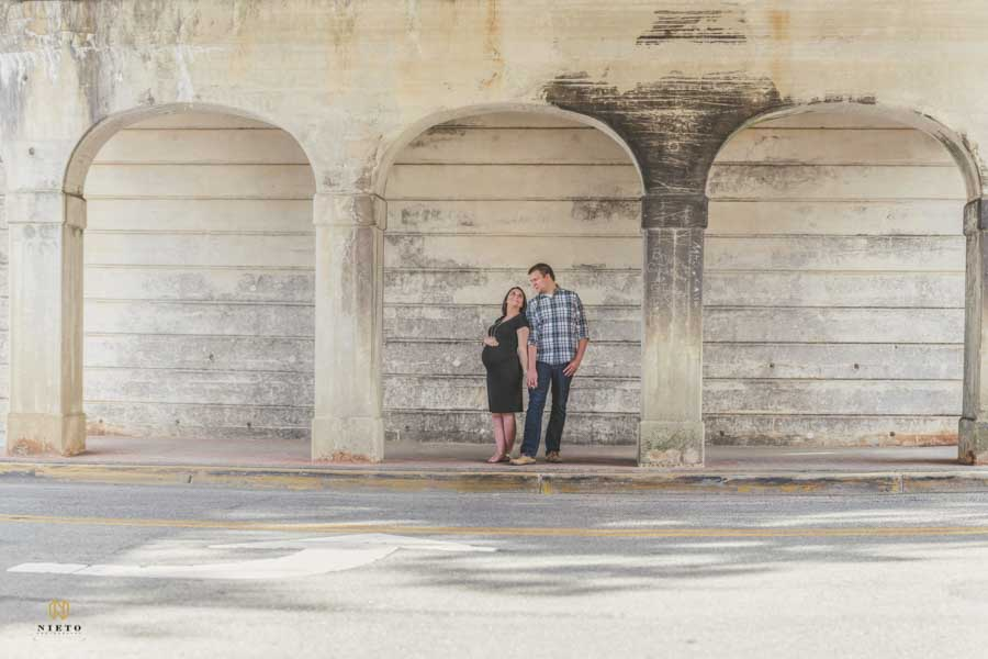 couple standing back to back posing for their Wake Forest maternity portrait