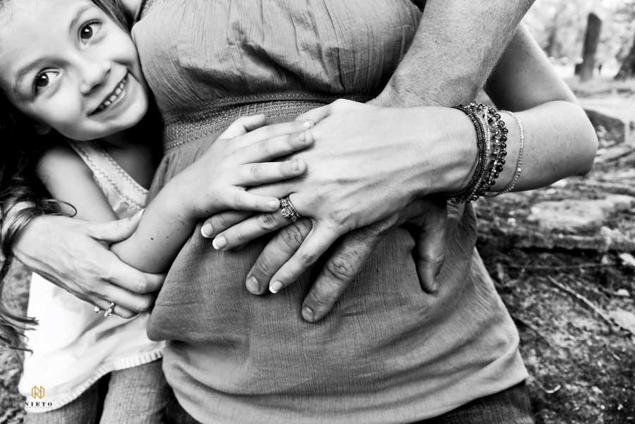 little girl smiling as she hugs her mothers stomach along with her mother and fathers hand