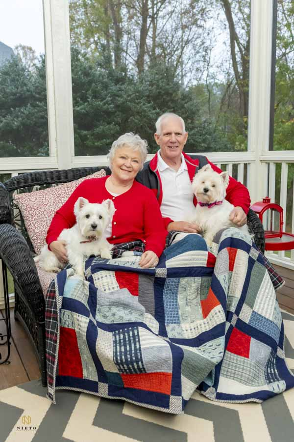 couple sitting on their back porch with their little dogs covered with a blanket