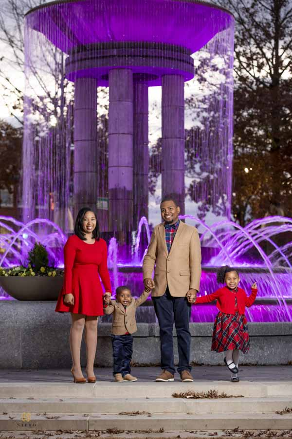 family holding hands and smiling for the camera in front of a water fountain with purple light