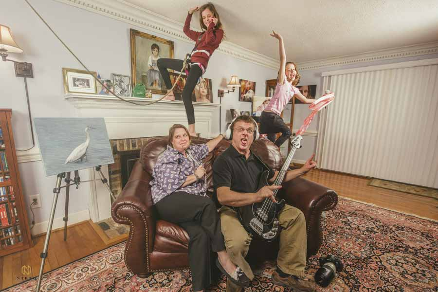 family of four posing for a crazy portrait in their living room