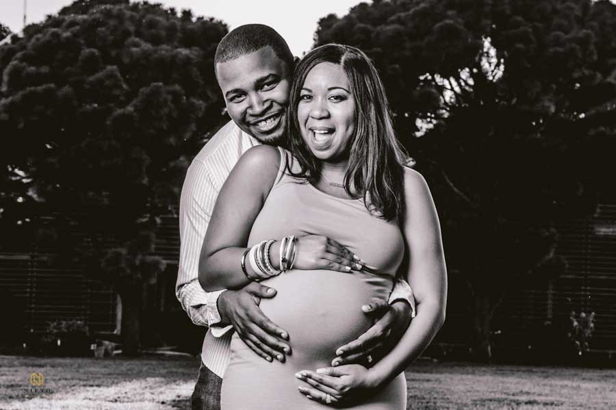 black and white image of happy parents posing for a Raleigh maternity portrait
