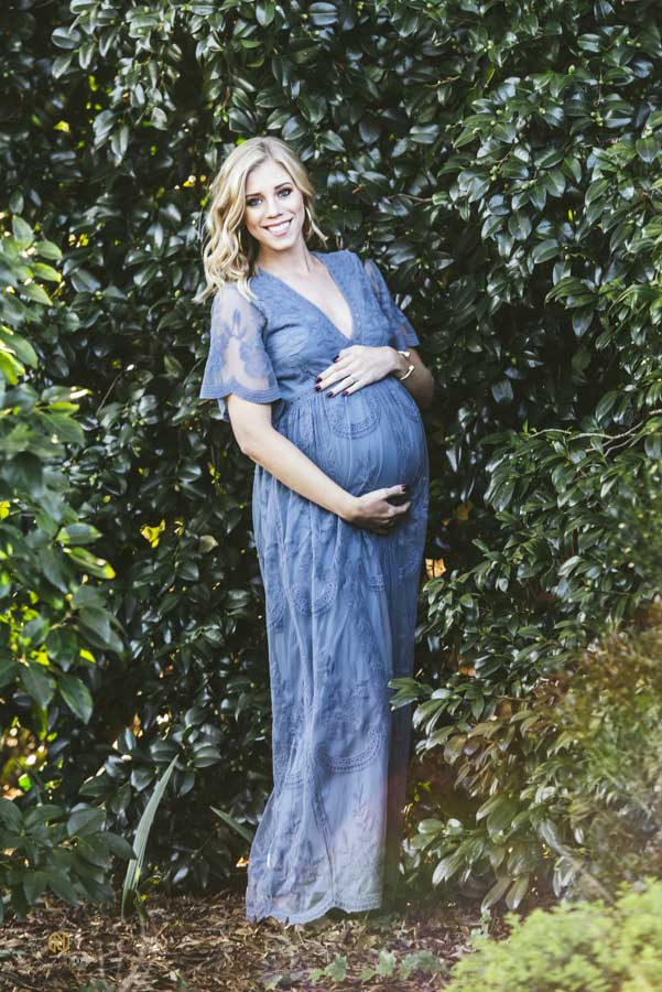 woman posing with her pregnant belly dressed in a blue gown