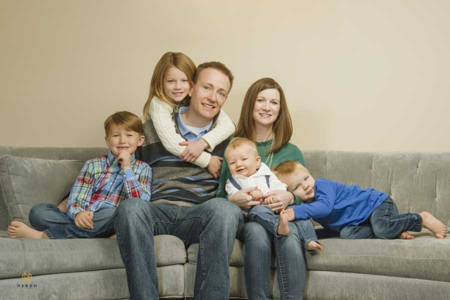 Raleigh family photography portrait in doors with a family of six sitting on a couch smiling