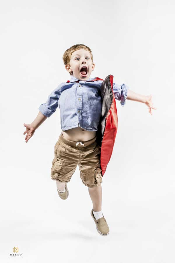little boy jumping with a cape on very happily