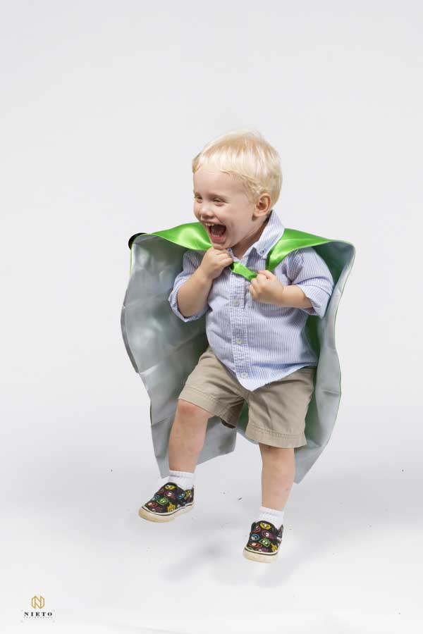little boy jumping off the ground with a green cape on