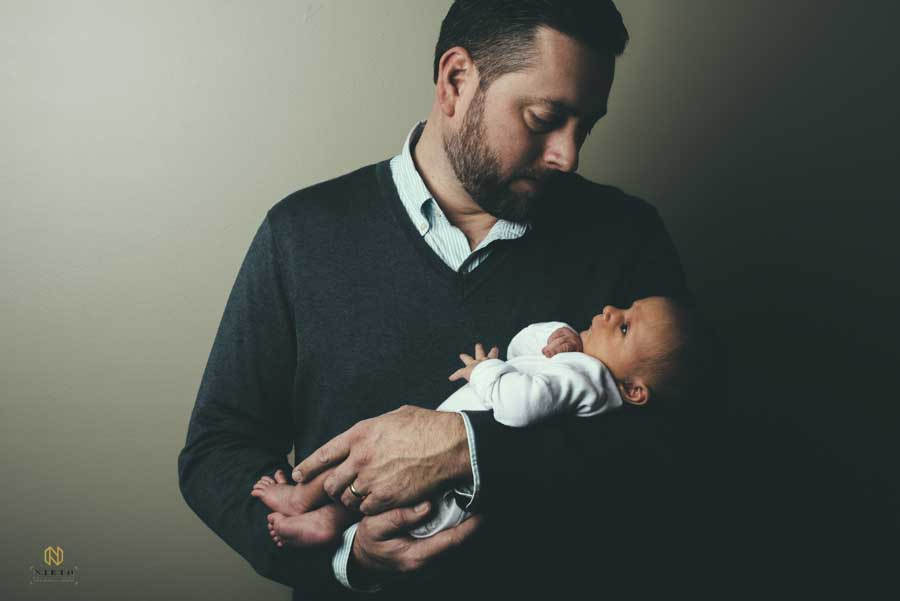 father in a sweater holding his little baby while standing against a wall