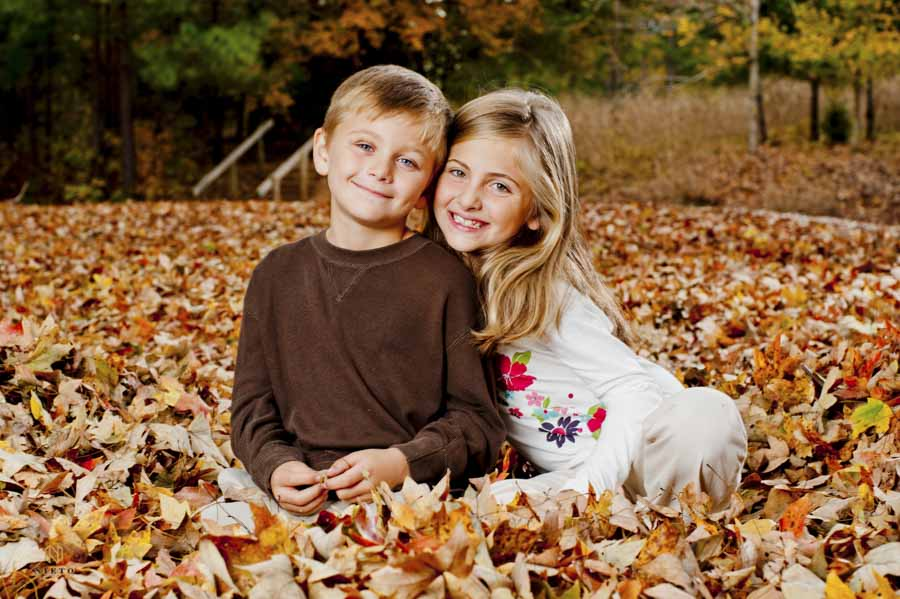 brother and sister sitting in fall leaves smiling or a Raleigh family portrait