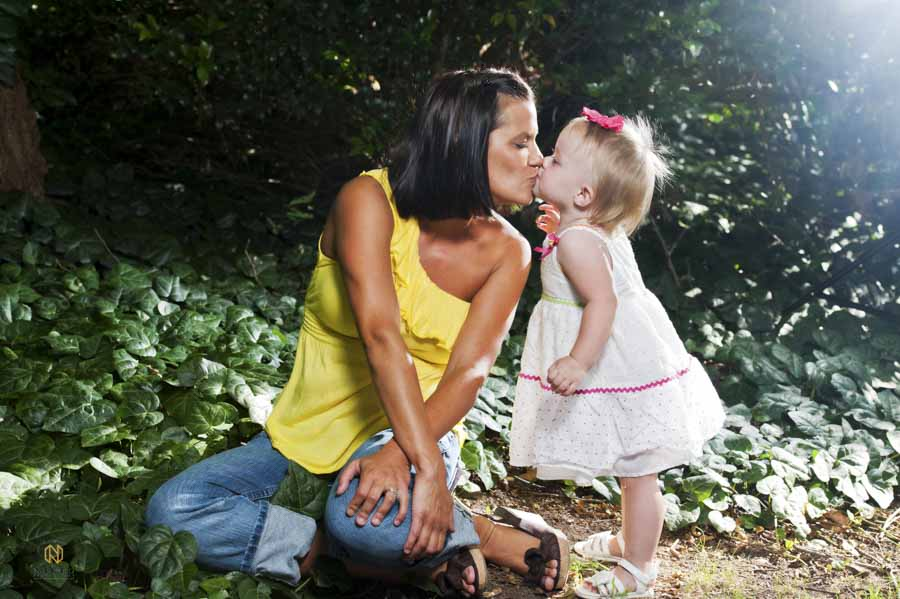 a mother and daughter kissing with ivy around them