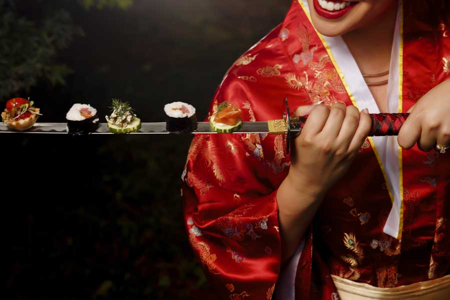 woman holding sword with sushi on it