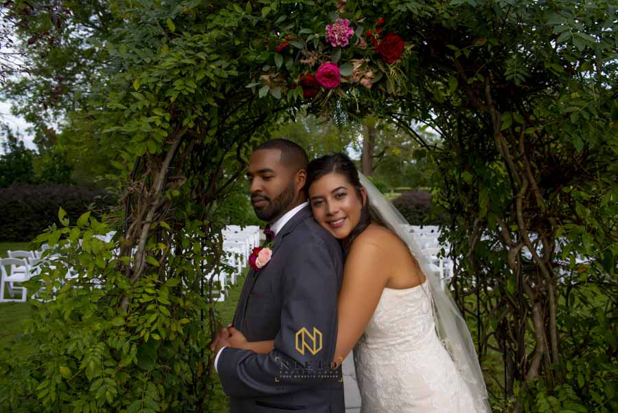 bride hugging her groom from behind posing for raleigh wedding photography portrait