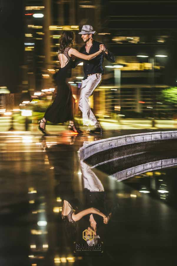 a couple dancing the tango with their reflection on the ground
