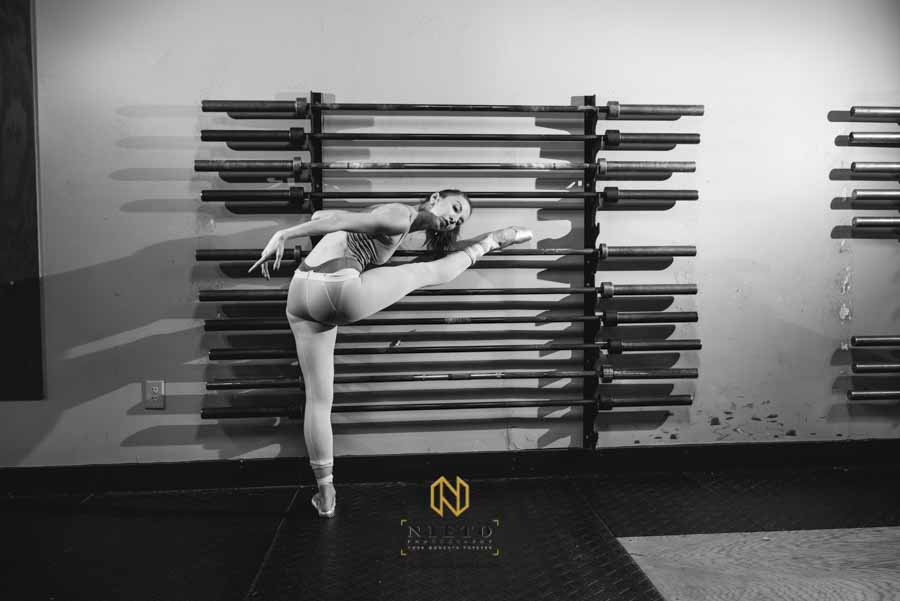black and white image of a ballet dancer stretching on weight lighting bars