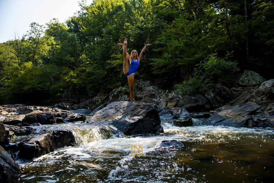 a woman in a blue leotard posing on a rock in the middle of the Eno River