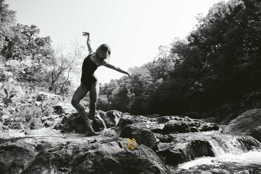 black and white portrait of a dancer on rocks beside a river