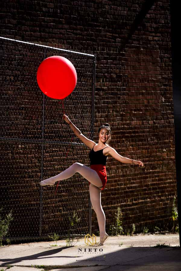 A dancer with a red balloon posing in an alley way