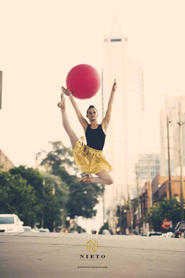 a ballerina in a gold dress jumping in the air in downtown Raleigh NC