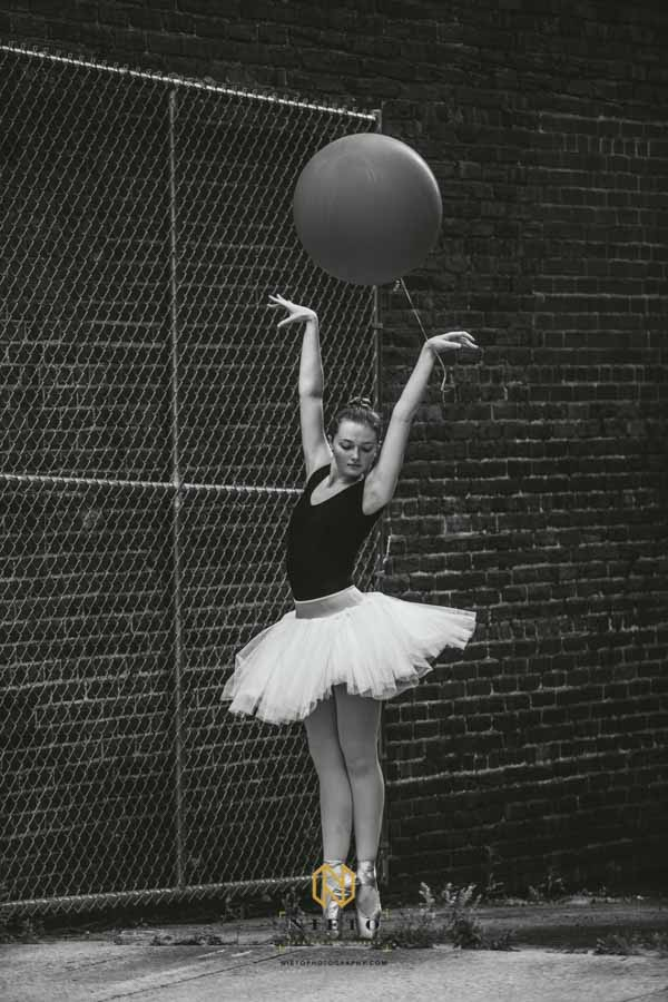 black and white image of a ballerina posing for a dance portrait with a balloon