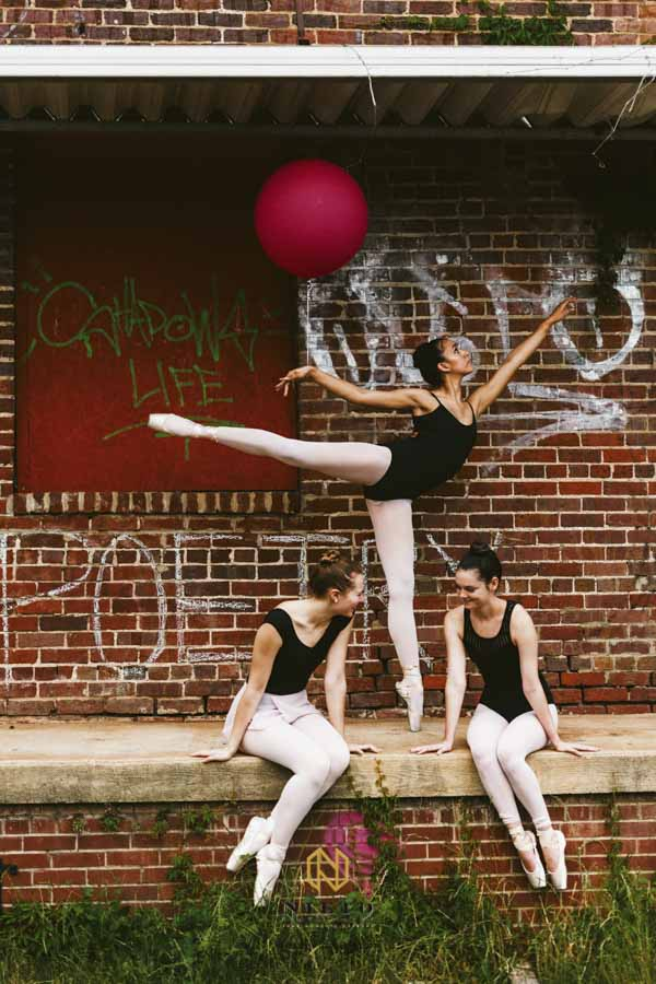 three ballerinas on a brick platform two are talking and the other is on point holding a balloon