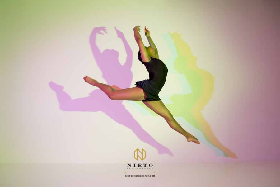 dancer jumping in the air with color shadows behind her