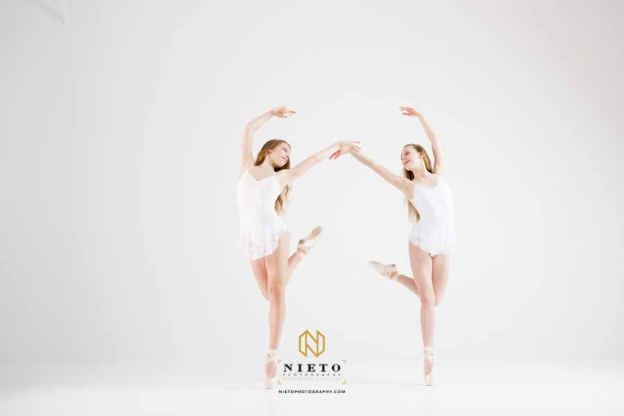 two dancers in white dancing in a white room
