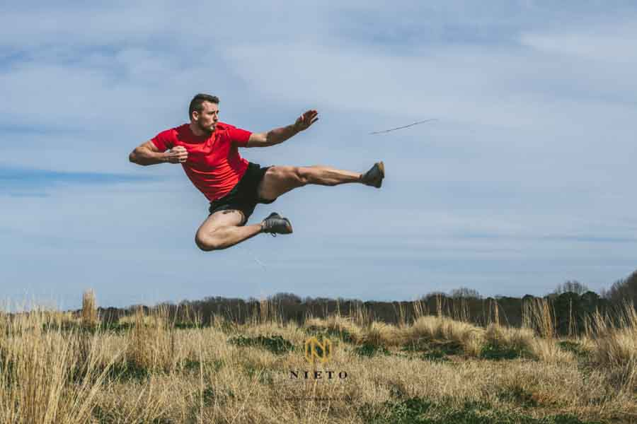 man jump kicking in the air in a field