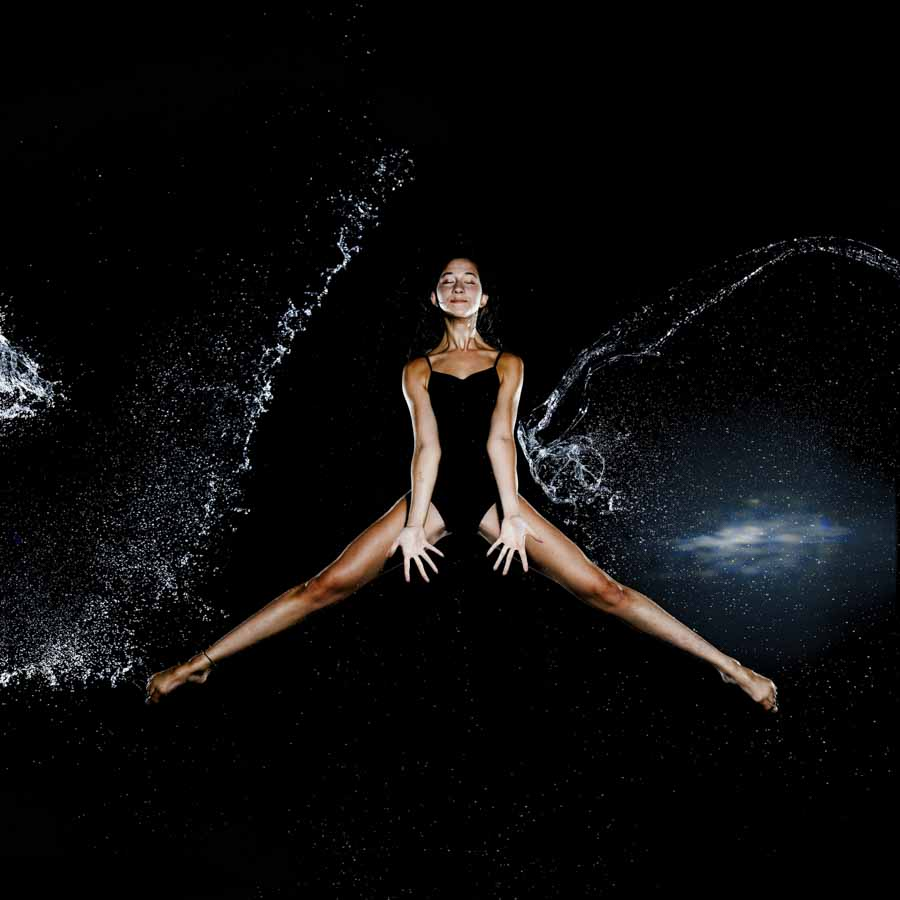 girl in black jumping in the air as water is hitting her for a fitness shoot