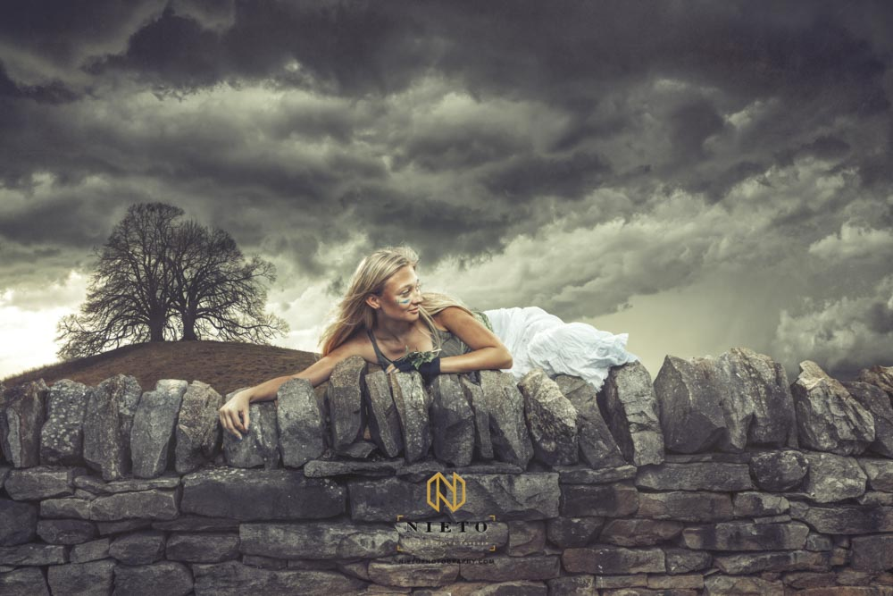 woman holding onto a wall with a tree and storm clouds behind her posing for a Raleigh Commercial Photographer