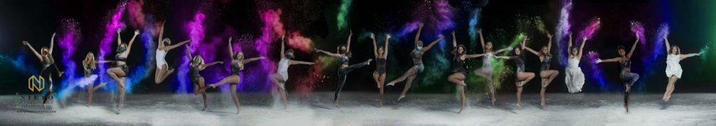 group portrait of dancers throwing colorful flour into the air