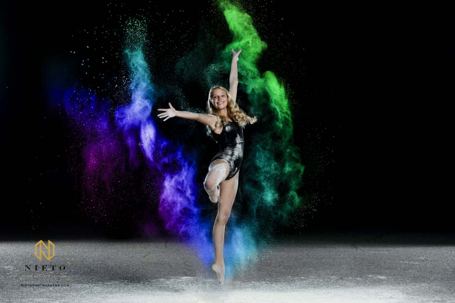 dancer dressed in black jumping in the air posing for a color flour dance shoot