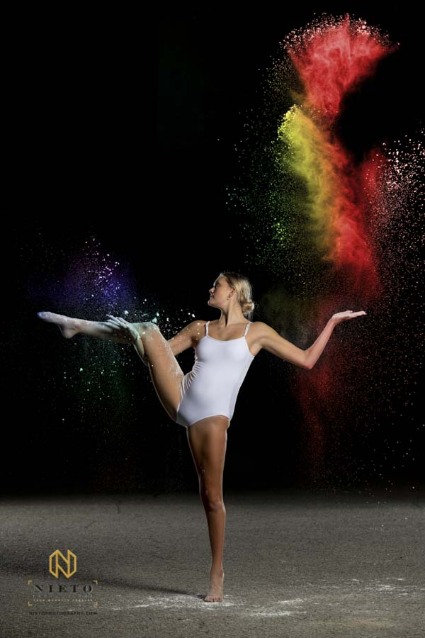 Dancer standing on one leg while throwing for the Color Flour Dance