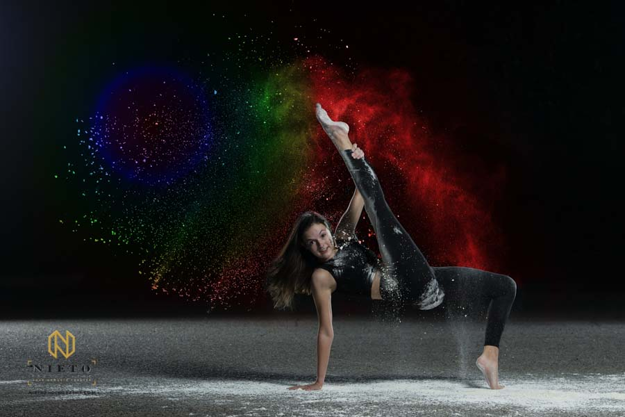 dancer supporting herself on one arm and one leg as she kicks other leg in the air