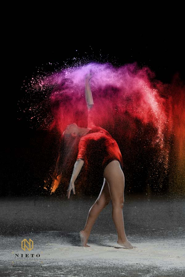 dancer tricking a pose as red flour falls on her