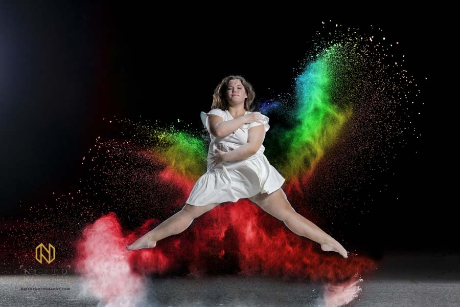 dancer in white jumping in the air with colored flour around her