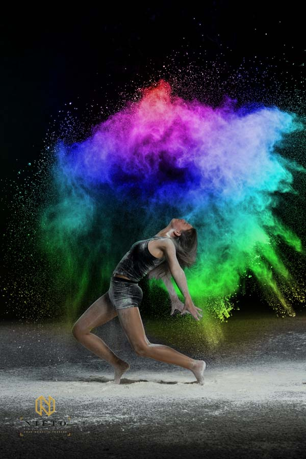 dancer throwing rainbow colored flour over herself and posing for the Color Flour Dance photoshoot