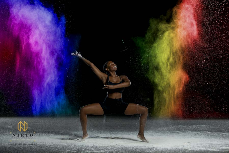 dancer smiling as she throws colorful flour in the air