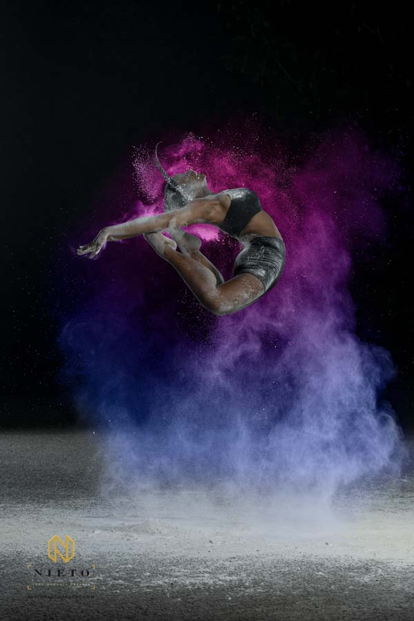 dancer jumping in the hair surrounded by a cloud of color