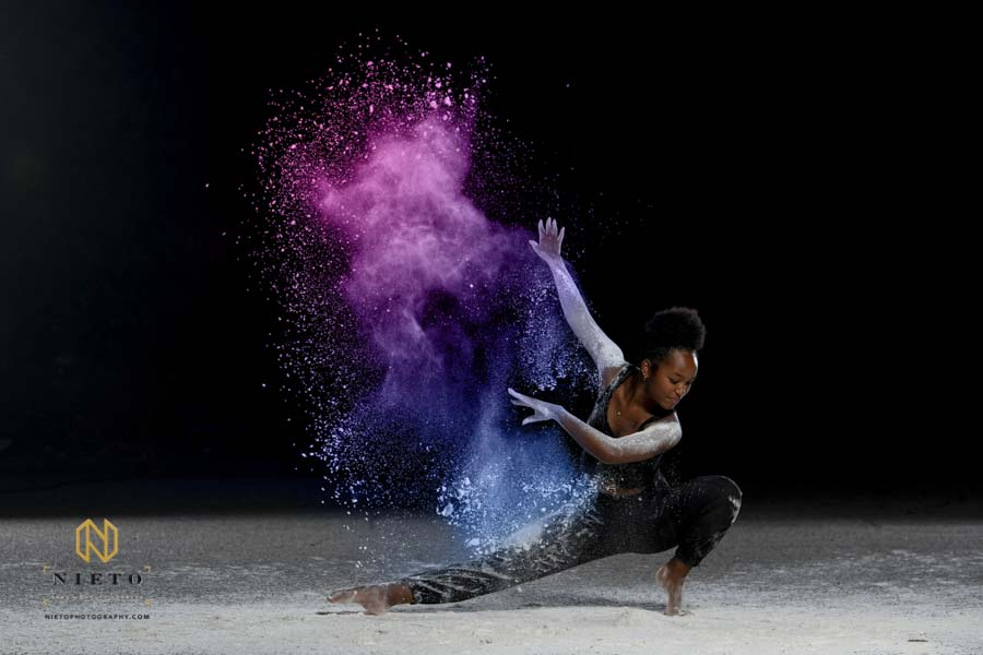 dancer bowing as she throws colorful dust behind her