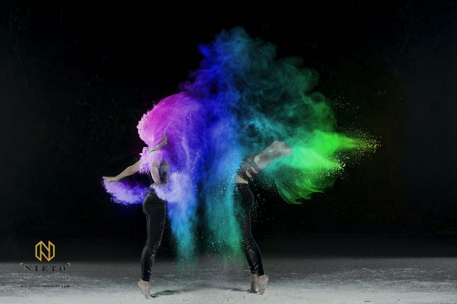 Two dancers on throwing colorful powder in the air as they dance