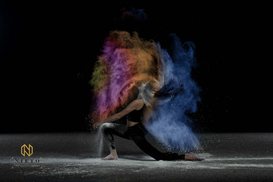 Dancer kneeling and throwing her hair back with colored powder in her hair