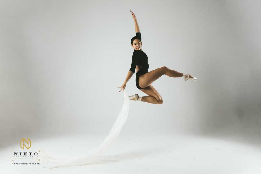 dancer jumping in the air dressed in black with a white cloth