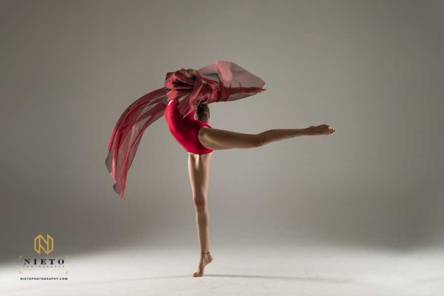 dancer posing with a red cloth while dressed in red