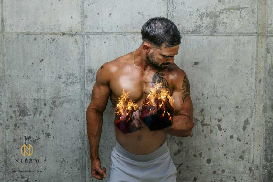 man doing bicep curls with a dumbbell that's on fire