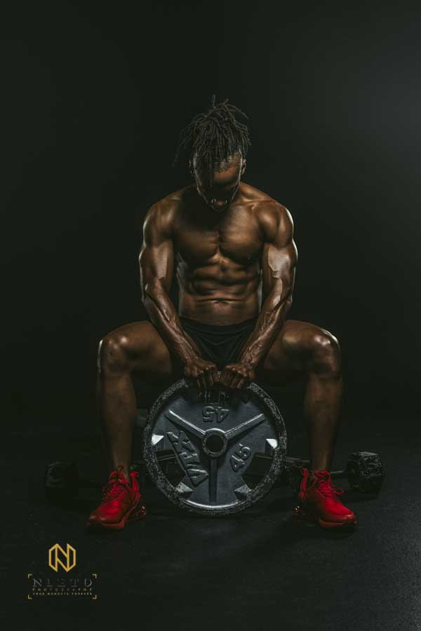 man posing on a black background while flexing holding a weightlifting plate