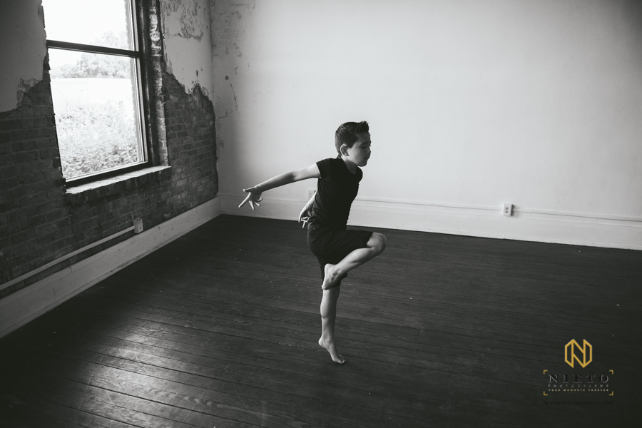 black and white image of a boy dancing in a studio