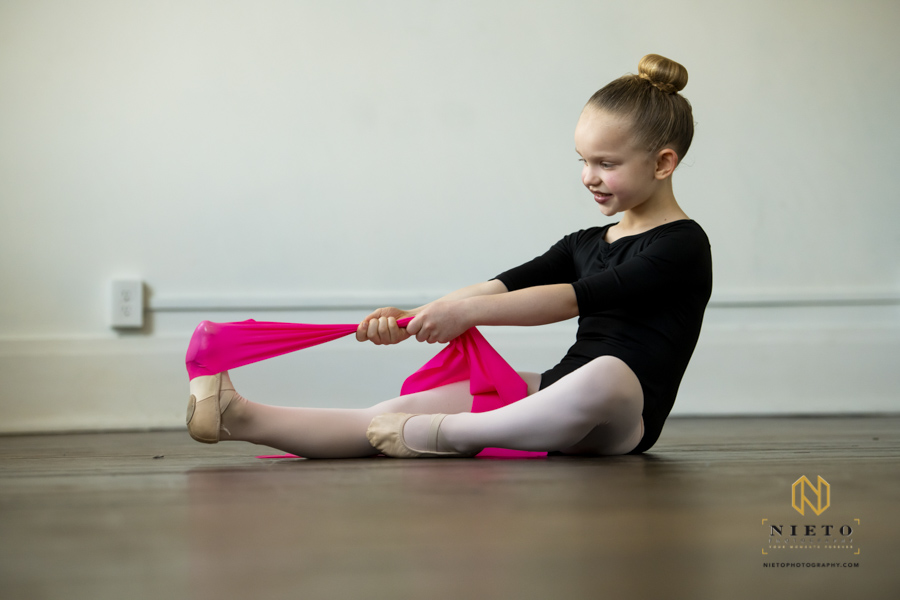 dancer pulling on pink band to stretch toes