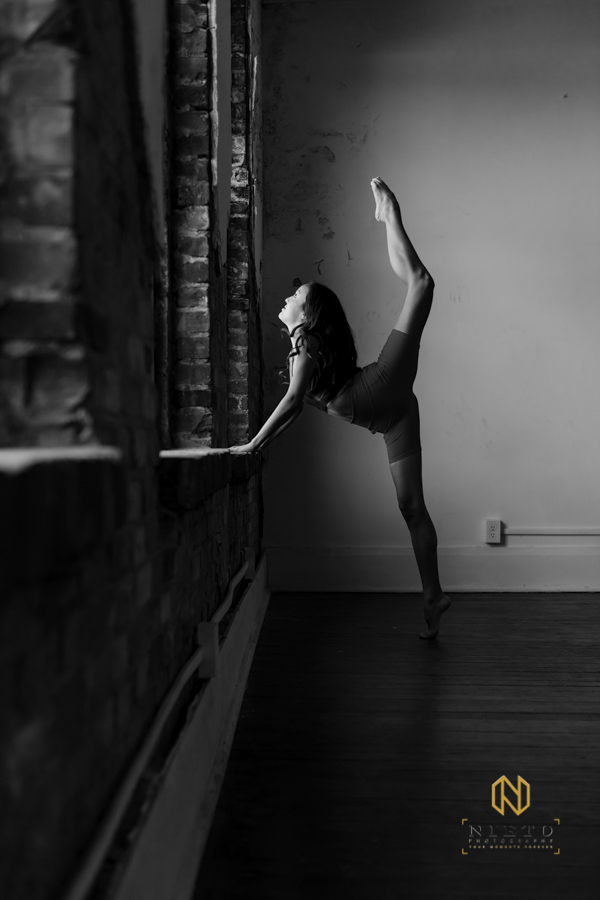 dancer stretching on a brick window with her leg above her head