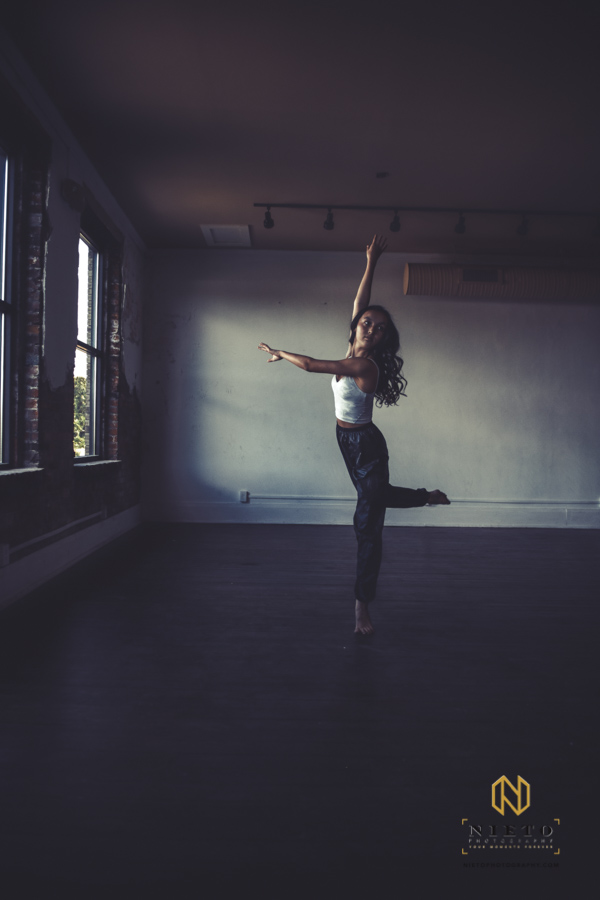dancer standing on white leg in a room with only window light