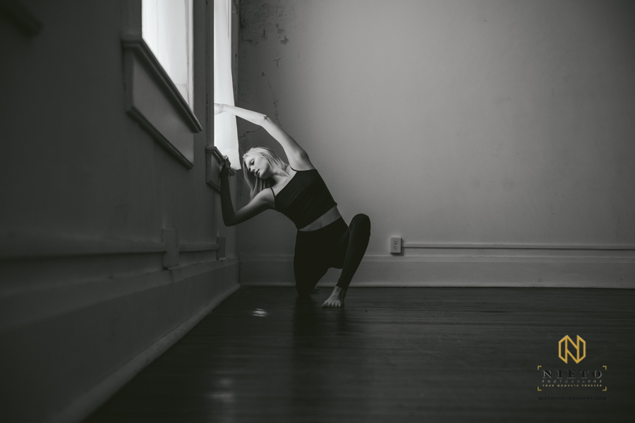 back and white image of dancer stretching under a window
