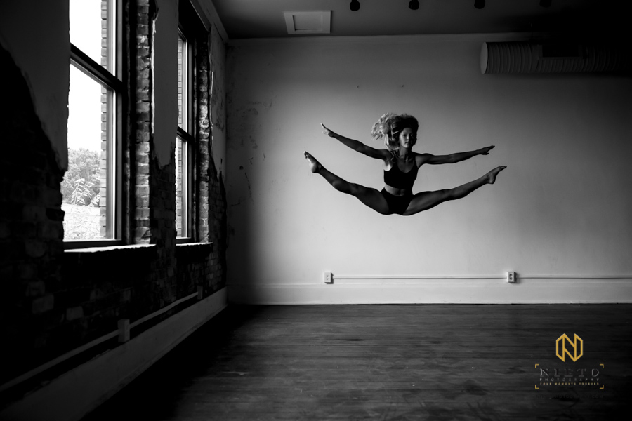 dancer doing a split in the air in a black and white image